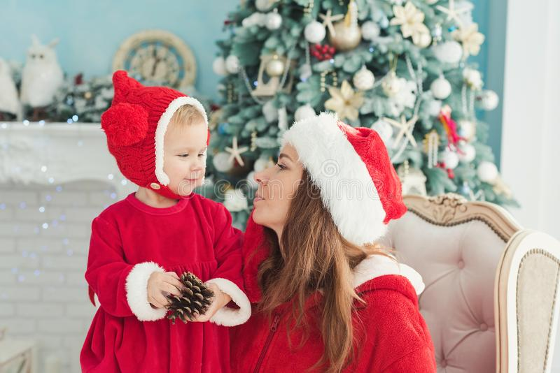 Happy mother and daughter in Christmas hats and in red dress sitting in armchair near fireplace and Christmas tree with gifts stock images