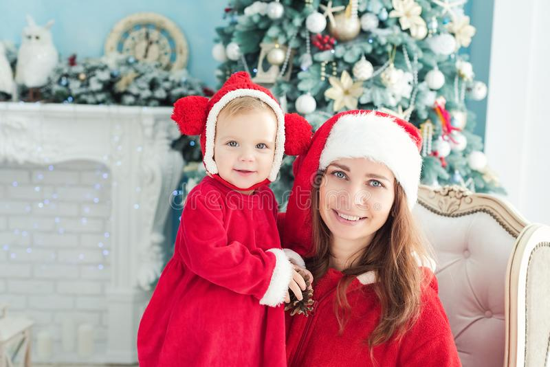 Happy mother and daughter in Christmas hats and in red dress sitting in armchair near fireplace and Christmas tree with gifts royalty free stock image