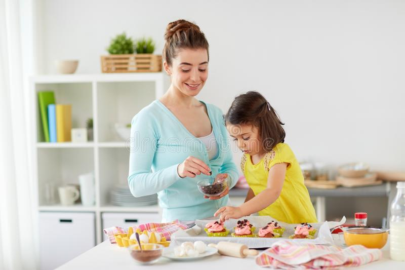 Happy mother and daughter cooking cupcakes at home royalty free stock image