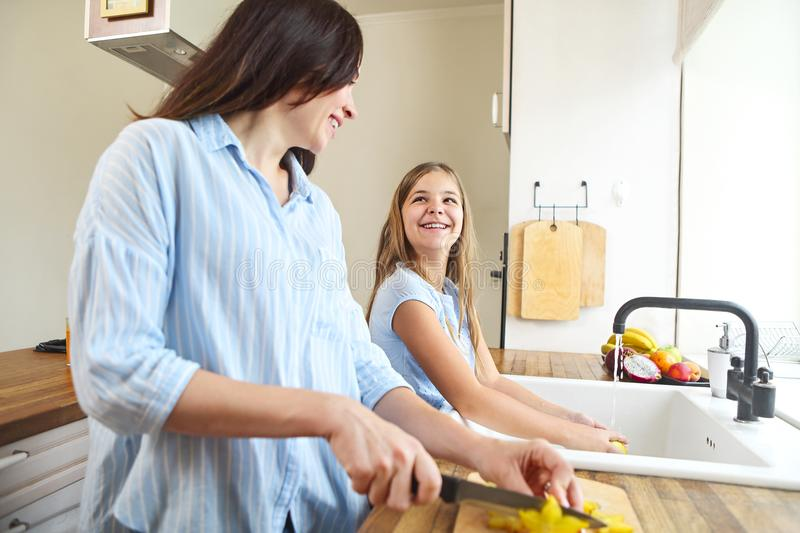 Happy mother and daughter cooking fruit salad at home kitchen royalty free stock photo