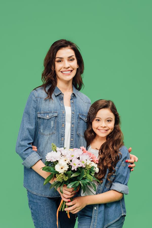 Happy mother and daughter in denim holding flowers and looking at camera isolated stock photography
