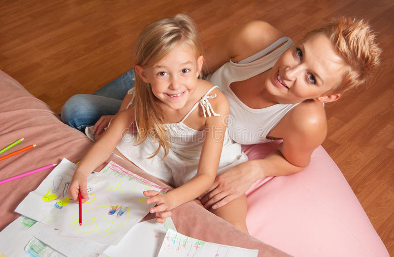 Happy mother and daughter drawing and having fun stock images
