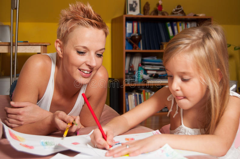 Happy mother and daughter drawing at their home royalty free stock images