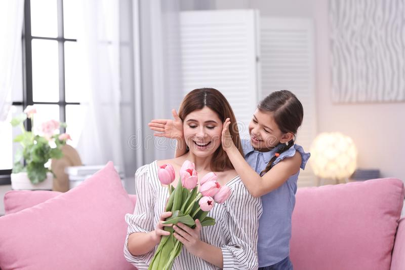 Happy mother and daughter with flowers at home stock photos