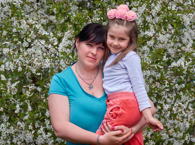 Happy mother and daughter in flowers stock image