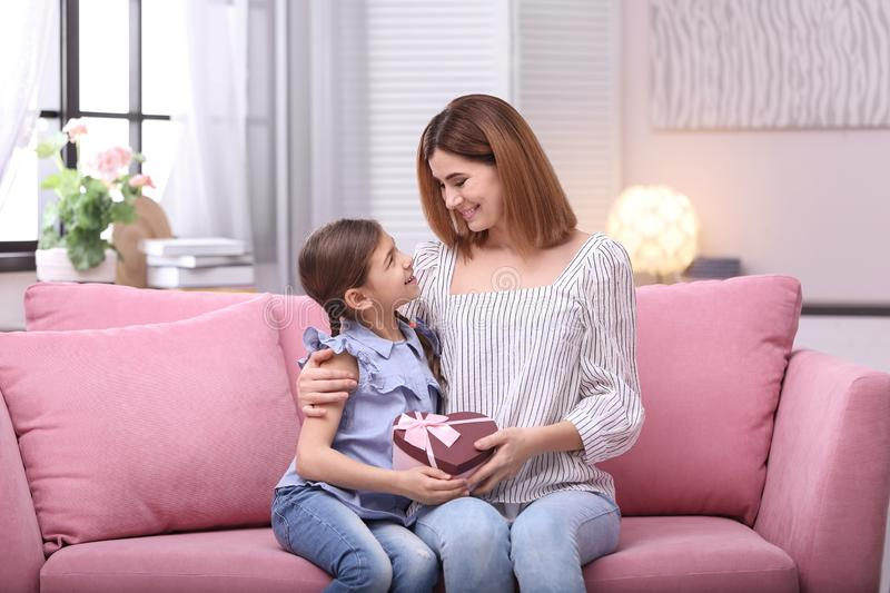 Happy mother and daughter with gift on sofa at home royalty free stock photography