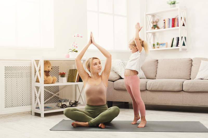Happy mother and daughter having yoga training at home royalty free stock photos