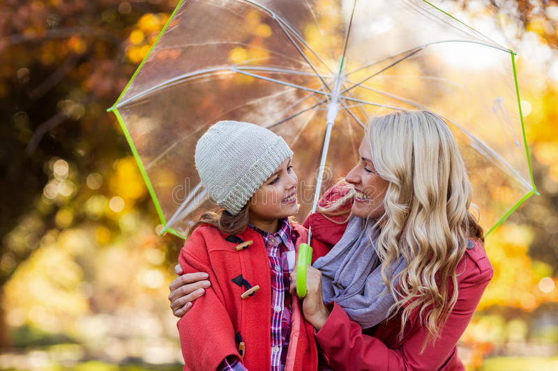 Happy mother and daughter holding umbrella at park royalty free stock photos