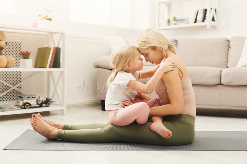Happy mother and daughter hugging while home yoga class. Happy mother and little daughter embracing while having home yoga class. Smiling girls in sportswear stock photography