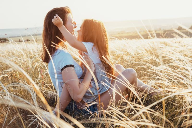 Happy mother and daughter hugging in summer field on sunset royalty free stock photography