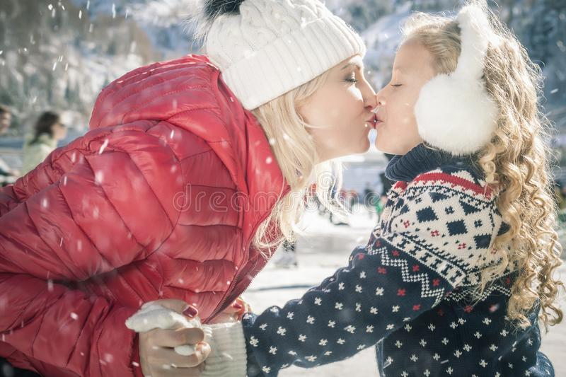 Happy mother and daughter kissing outdoor, ice skating at Christmas. Happy mother and daughter kissing outdoor, ice skating at ice rink. Mother and daughter has stock images