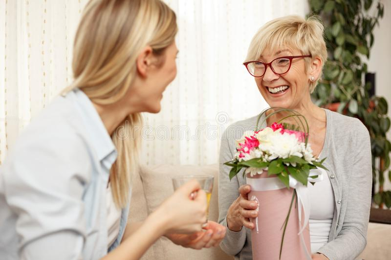 Mother and daughter enjoying conversation in living room stock photos