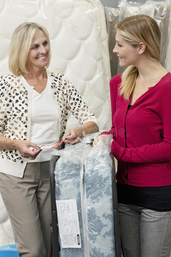 Happy mother and daughter looking at each other in furniture store stock images