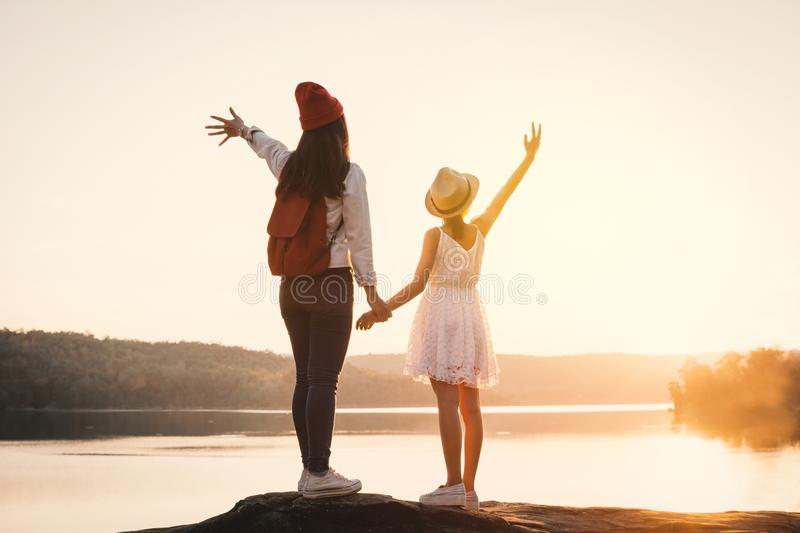 Happy mother and daughter looking at the sky during sunset royalty free stock photos