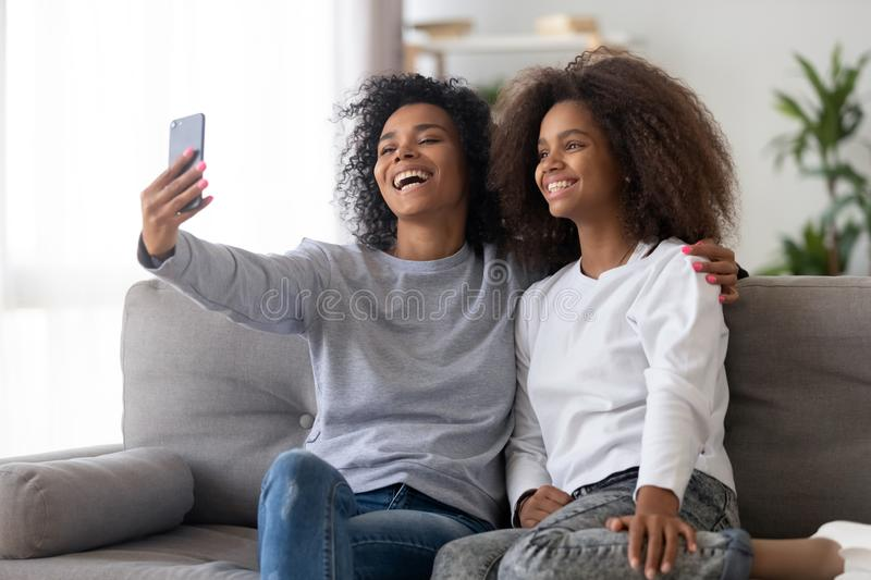 Happy mother and daughter make selfie together stock photos
