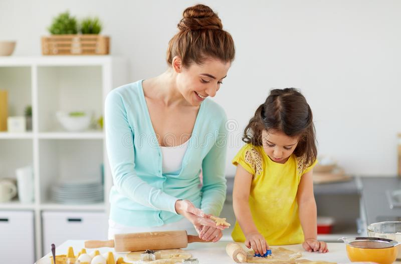 Happy mother and daughter making cookies at home. Family, cooking and people concept - happy mother and little daughter with molds making cookies from dough at stock photos