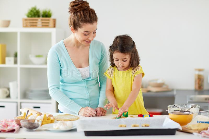 Happy mother and daughter making cookies at home. Family, cooking and people concept - happy mother and little daughter with molds making cookies from dough at royalty free stock photos
