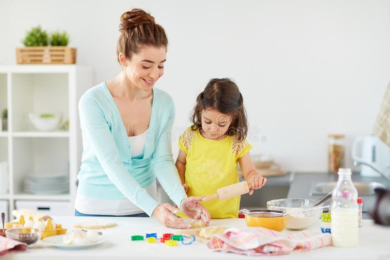Happy mother and daughter making cookies at home. Family, cooking and people concept - happy mother and little daughter with rolling pin making cookies from stock image