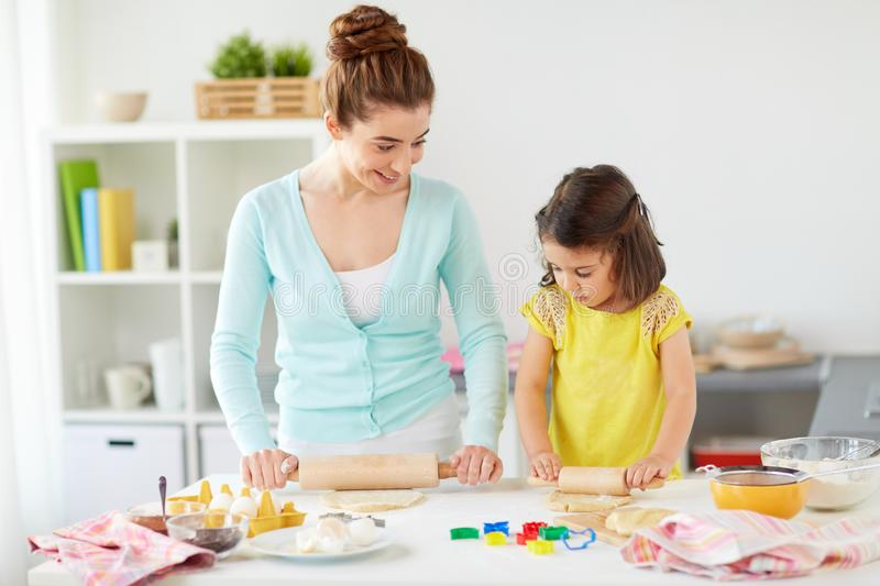 Happy mother and daughter making cookies at home. Family, cooking and people concept - happy mother and little daughter with rolling pins making cookies from royalty free stock image
