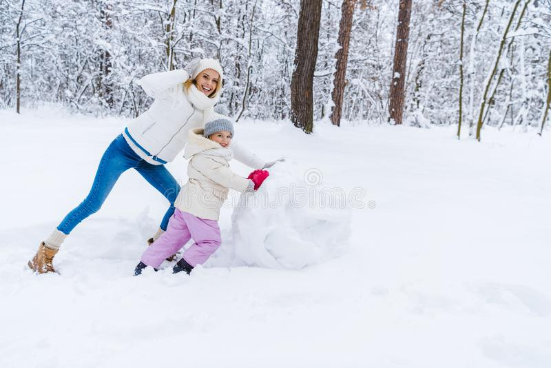 happy mother and daughter making snowman royalty free stock image