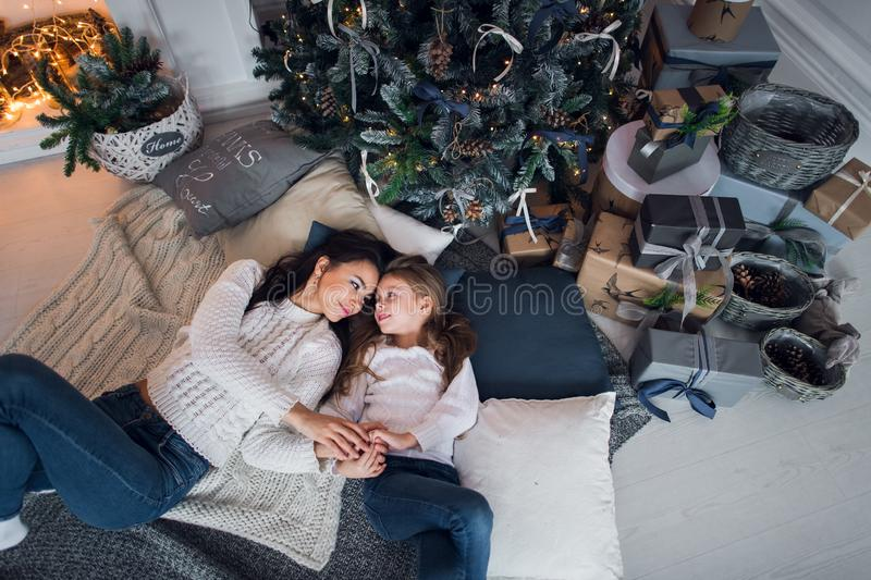 Happy mother and daughter opening Christmas gifts. Family gathered around a tree at home. Christmas tree with presents royalty free stock photo