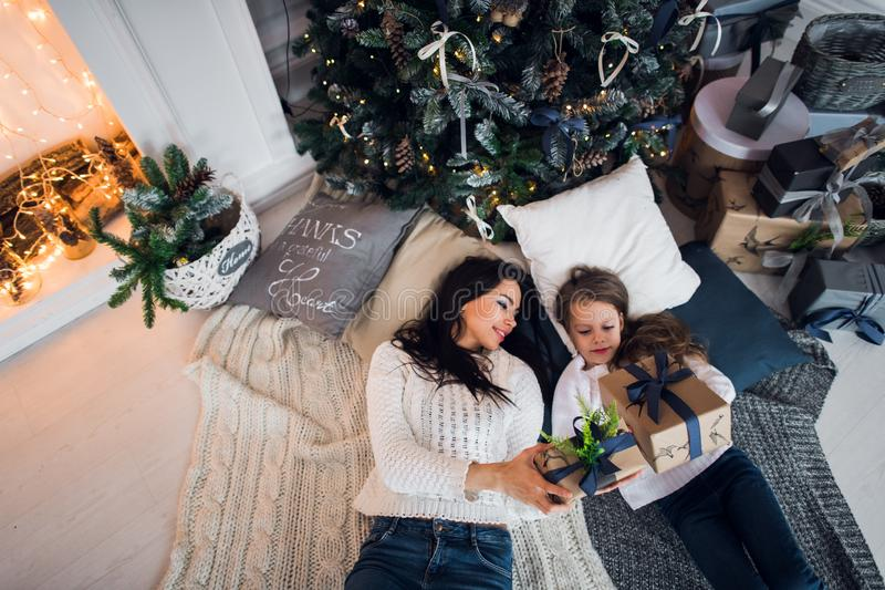 Happy mother and daughter opening Christmas gifts. Family gathered around a tree at home. Christmas tree with presents stock photo