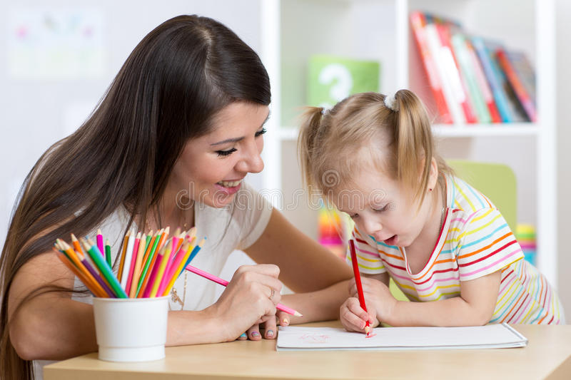 Happy mother and daughter painting with pencils royalty free stock photo