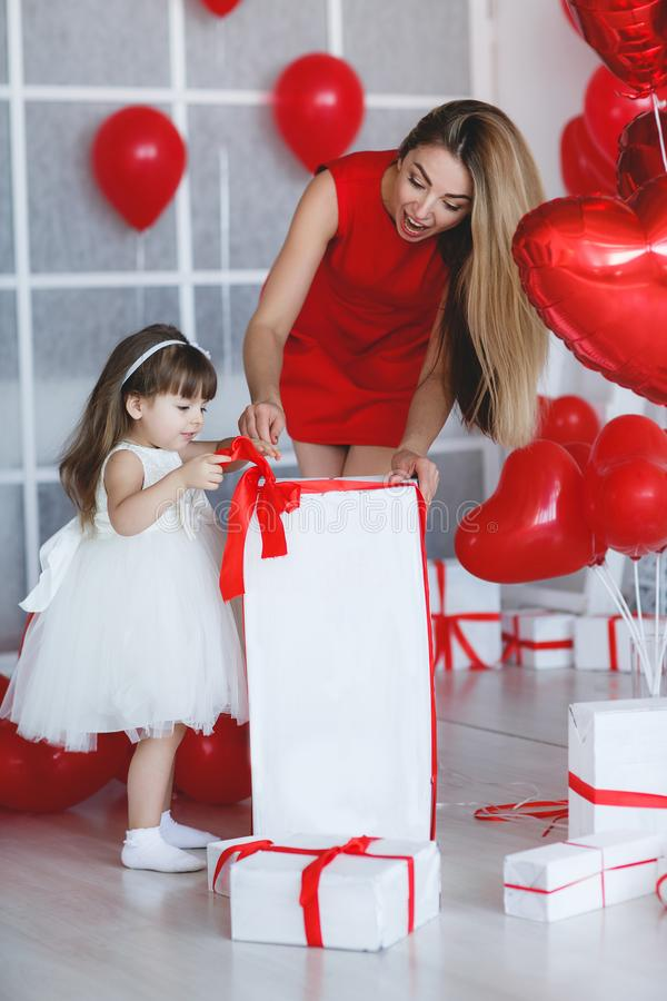 Happy mother and daughter parses gifts on Valentine`s Day. Young beautiful mother and her little daughter,dressed in a beautiful,festive and elegant dress royalty free stock photos