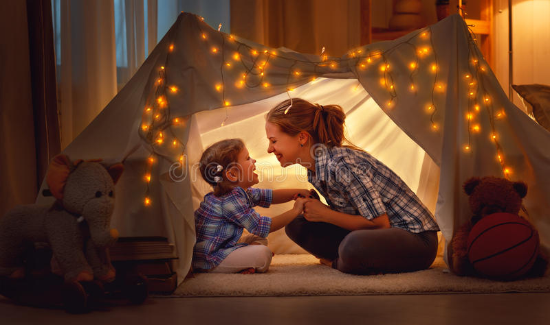 Happy mother and daughter playing at home in tent royalty free stock photo