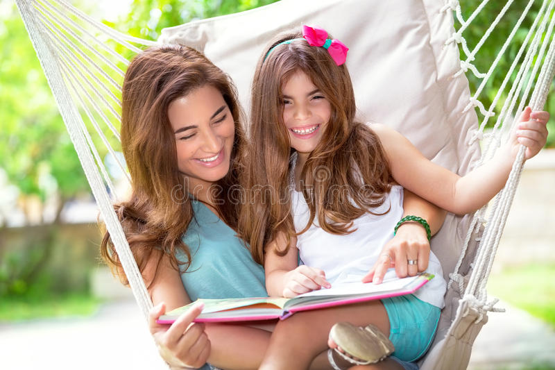 Happy mother with daughter. Portrait of beautiful happy mother with cute little daughter sitting on backyard in hammock and reading funny story, nice lovely stock photos