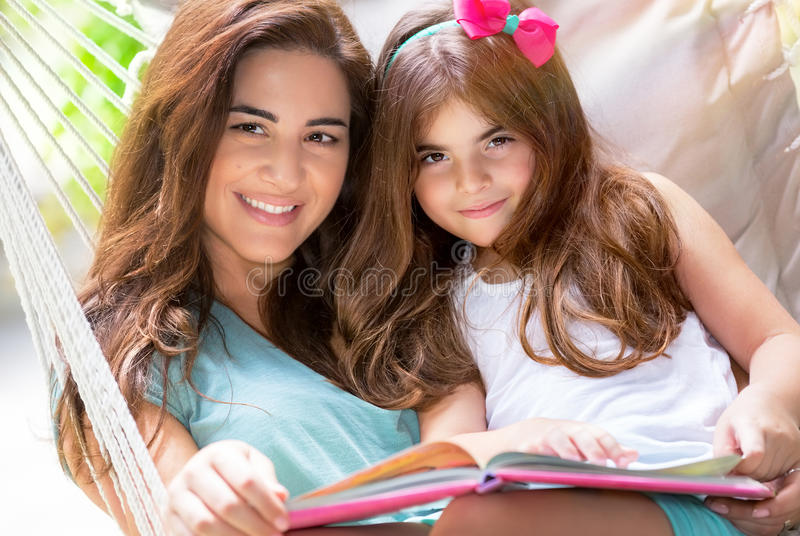 Happy mother with daughter. Portrait of beautiful happy mother with cute little daughter sitting on backyard in hammock and reading interesting book, nice lovely stock photography