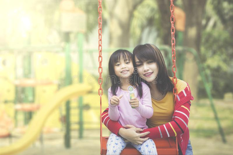 Happy mother and daughter posing at playground stock images