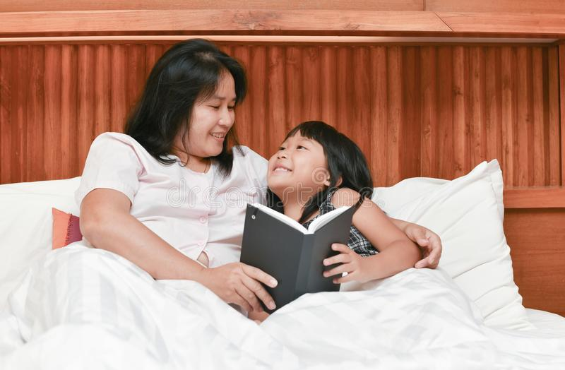 Happy mother and daughter reading book on bed royalty free stock photography