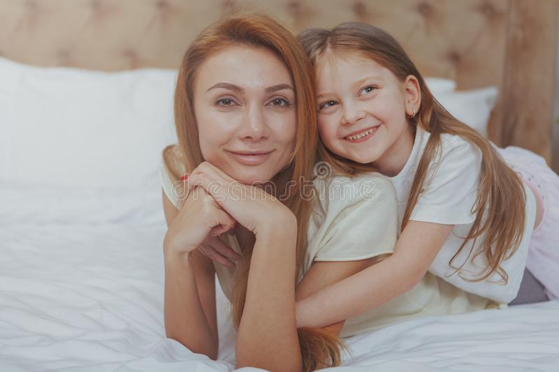 Happy mother and daughter resting at home together stock images