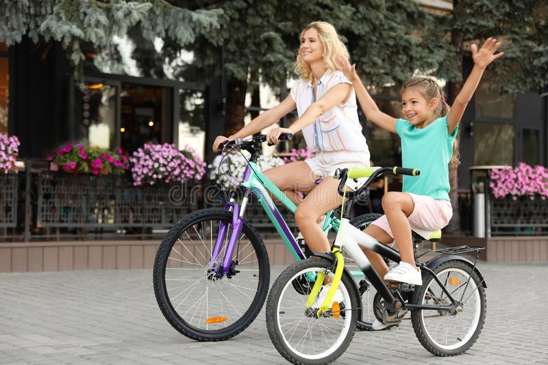 Happy mother with daughter riding  in city. Happy mother with daughter riding bicycles in city stock photography