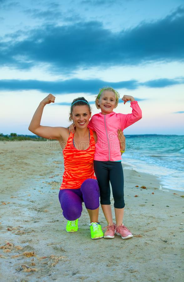 Happy mother and daughter on seashore in evening showing biceps royalty free stock photography
