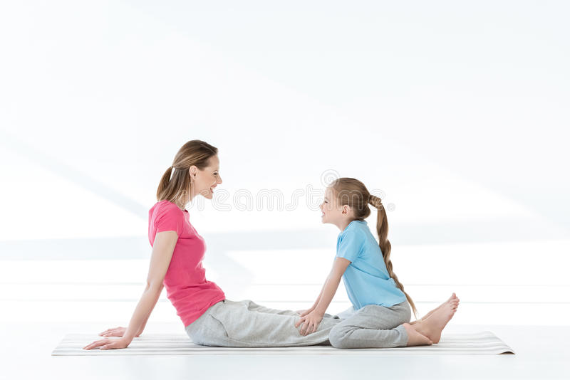 Happy mother and daughter sitting on yoga mat and looking at each other stock photos