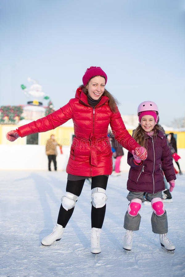 Happy mother and daughter are skating atoutdoor skating rink. Happy mother and daughter are skating at the outdoor skating rink in winter stock photo