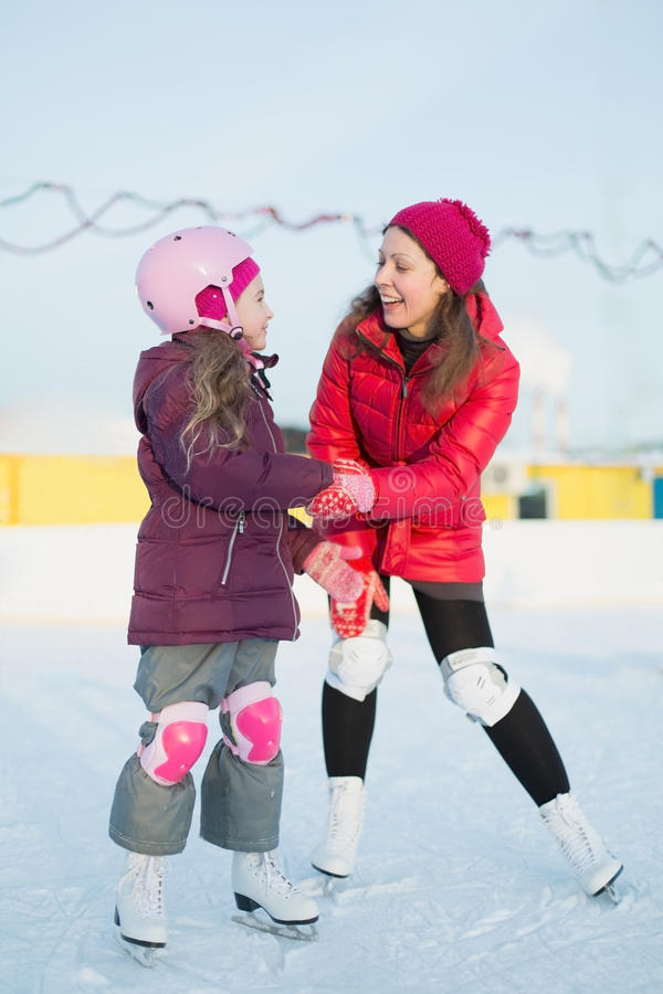 Happy mother and daughter are skating at the outdoor rink stock photos