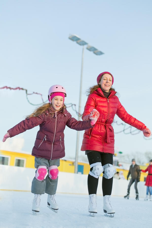 Happy mother and daughter are skating at outdoor skating rink. Happy mother and daughter are skating at the outdoor skating rink in winter royalty free stock photos