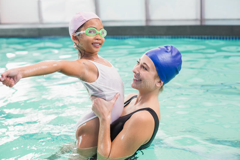 Happy mother and daughter in the swimming pool stock photography
