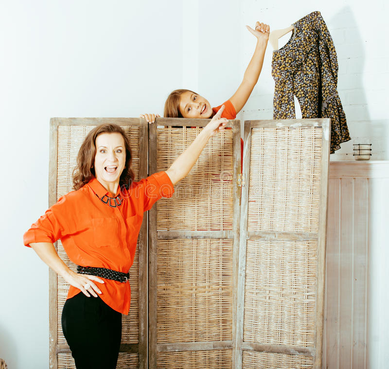 Happy mother with daughter trying on dresses at home interior, h royalty free stock photos