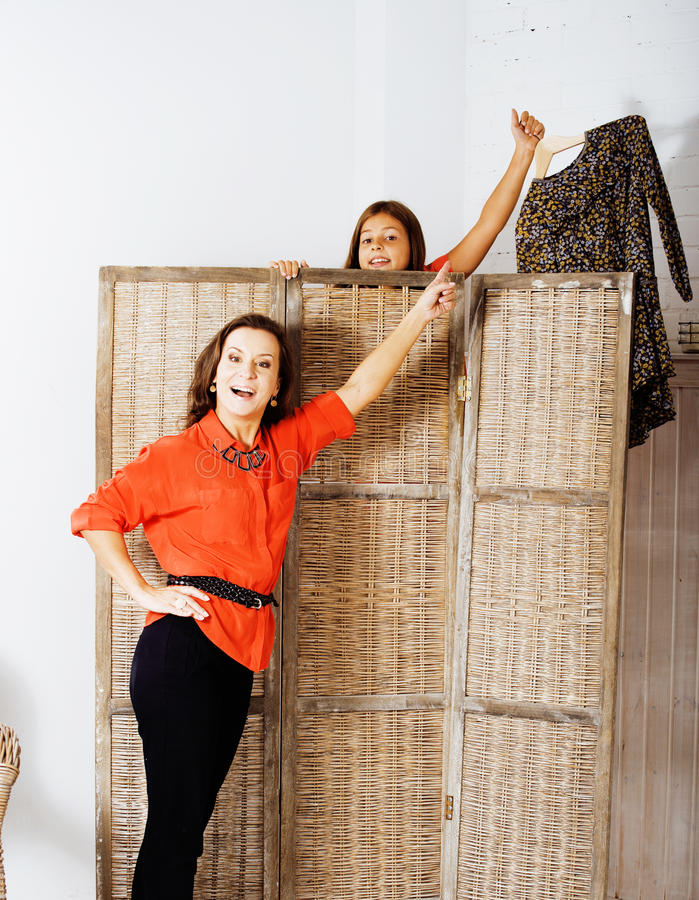 Happy mother with daughter trying on dresses at home interior, h stock image