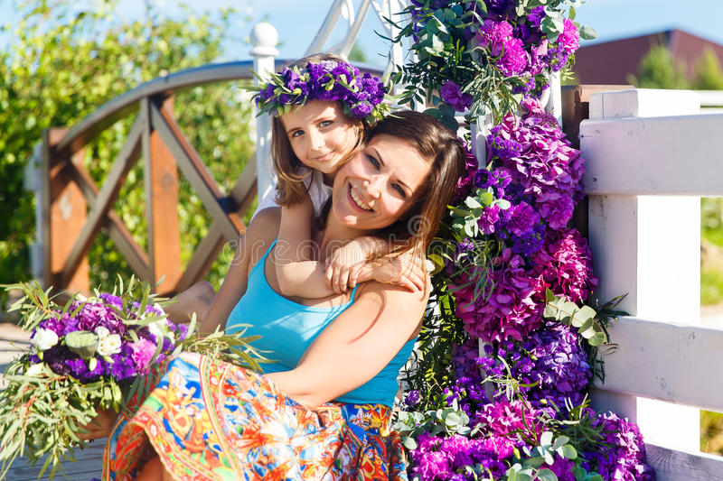Happy mother and daughter under the arch for the wedding ceremony. Floristic composition in vintage style. The Provence. royalty free stock photo