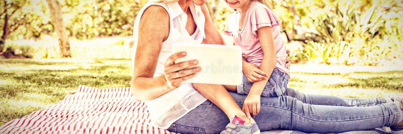 Happy mother and daughter using digital tablet in park royalty free stock photos