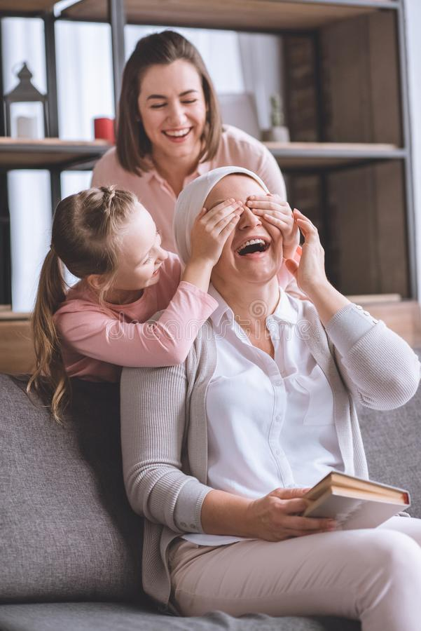 Happy mother and daughter visiting sick smiling grandmother in kerchief reading book. At home royalty free stock images