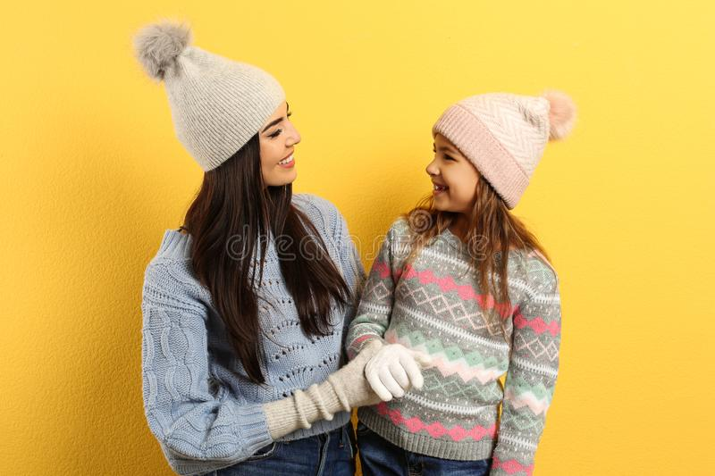Happy mother and daughter in warm clothes on background. Winter vacation royalty free stock photo