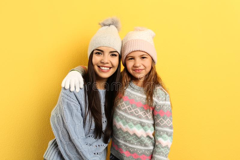 Happy mother and daughter in warm clothes on background. Winter vacation stock images