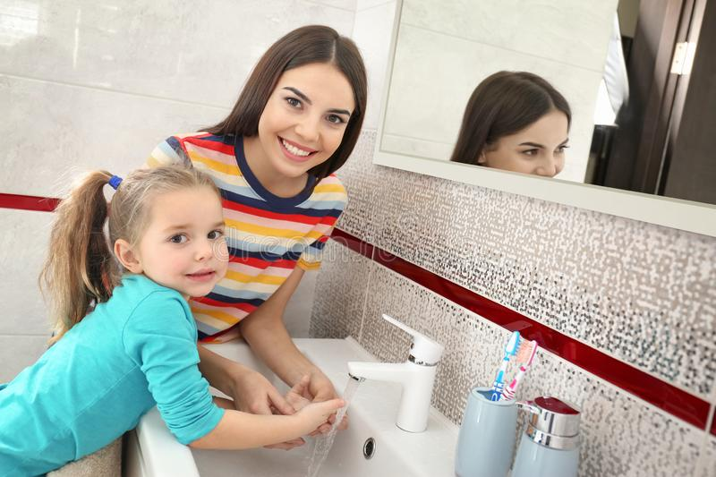Happy mother and daughter washing hands in bathroom royalty free stock image