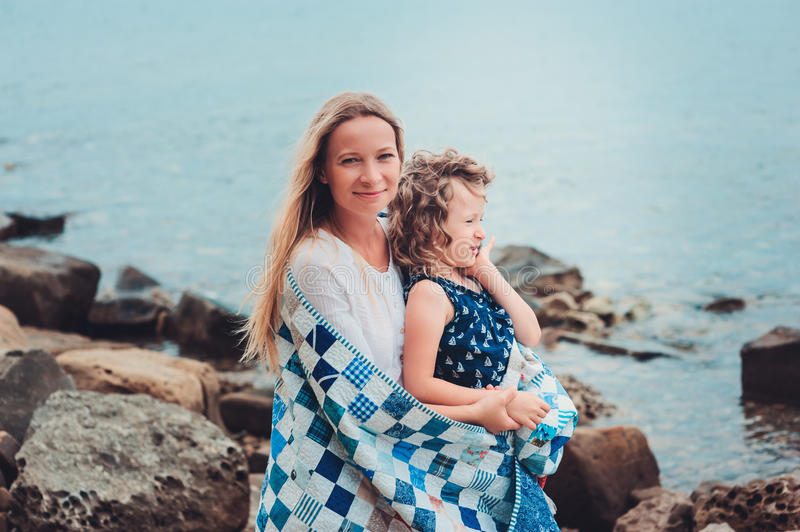 Happy mother and daughter wrapped in quilt blanket spending time together on the beach on summer vacation. Happy family traveling royalty free stock images